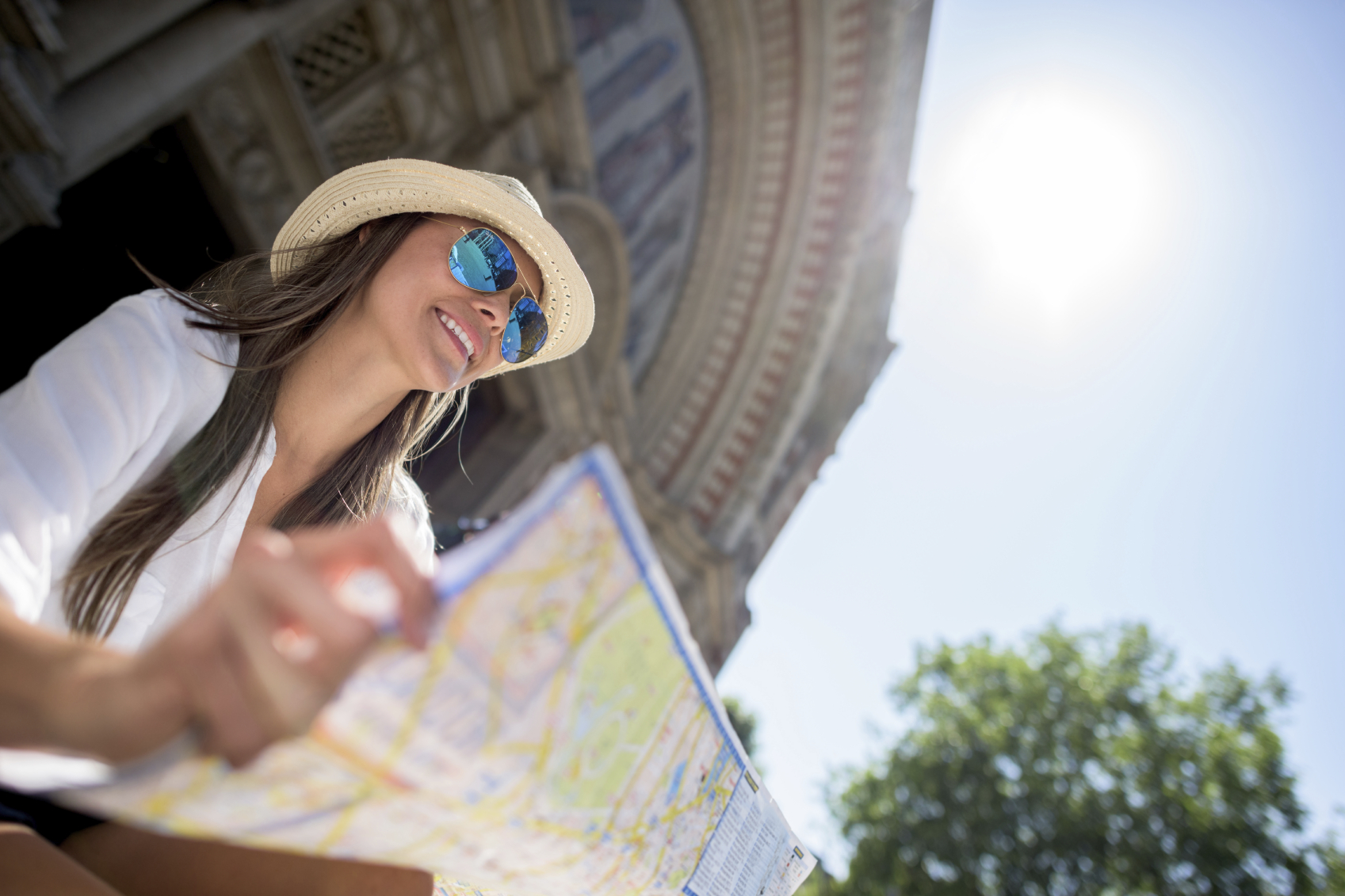 Happy woman tourist sightseeing and holding a map while traveling on her summer vacations